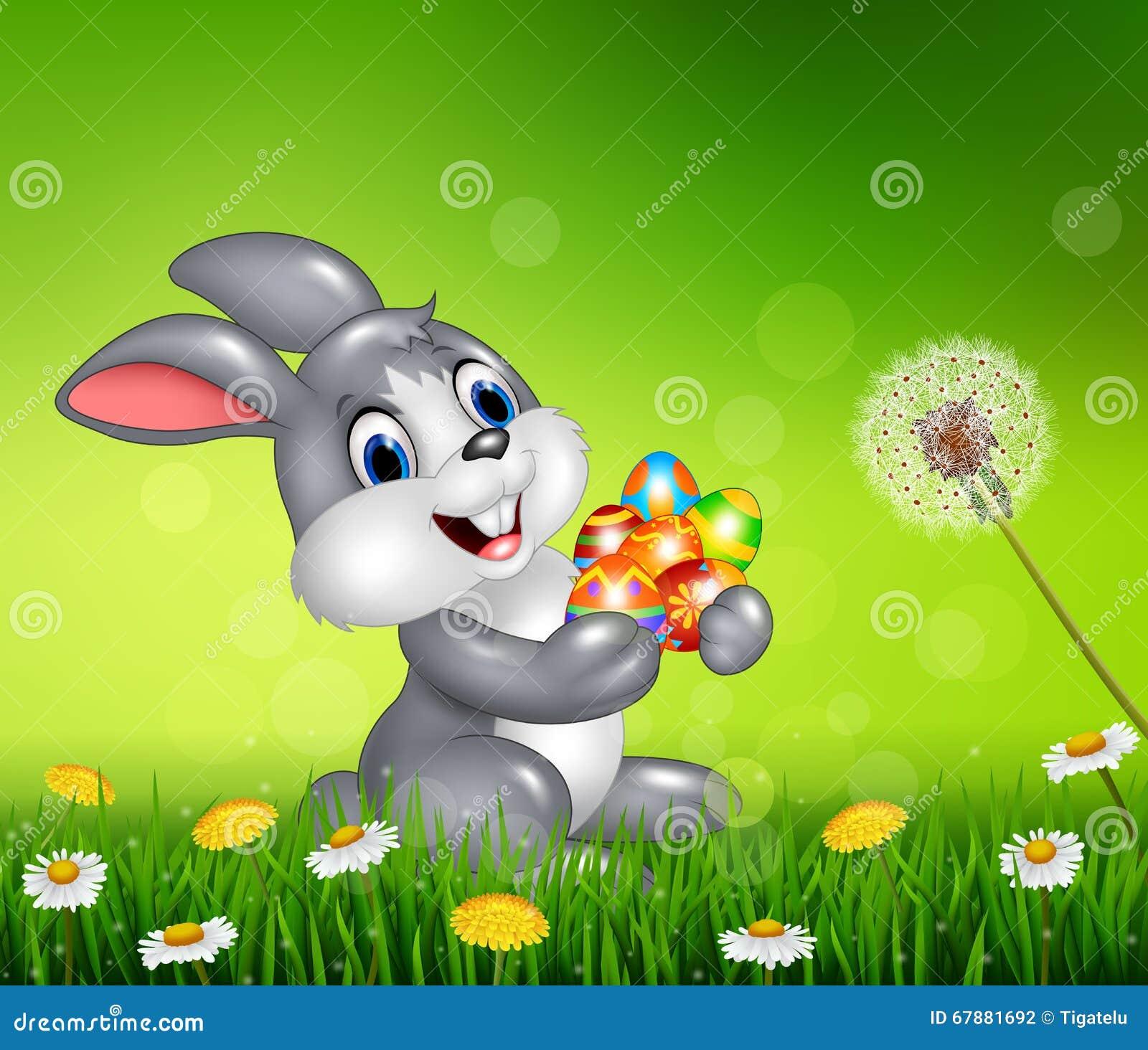 愉快的小的兔宝宝用五颜六色的复活节彩蛋
