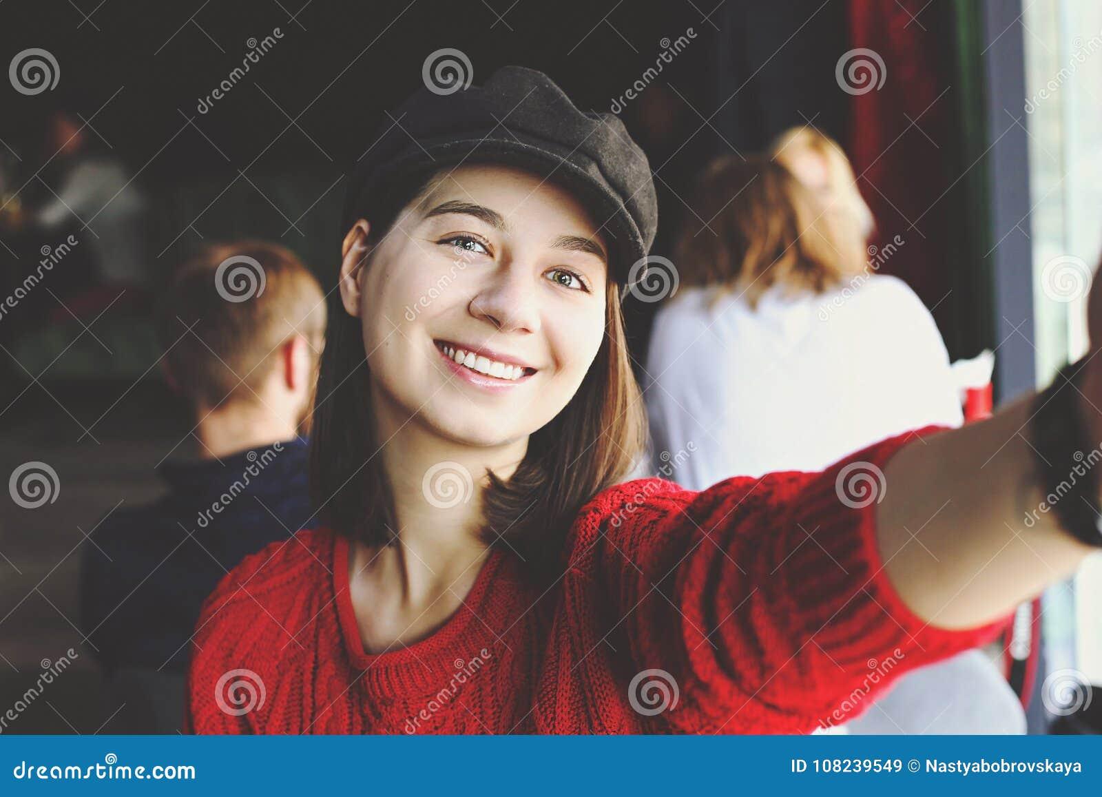愉快的少妇饮用的热奶咖啡,拿铁, macchiato,茶,使用片剂计算机和谈话在咖啡店/ba的电话