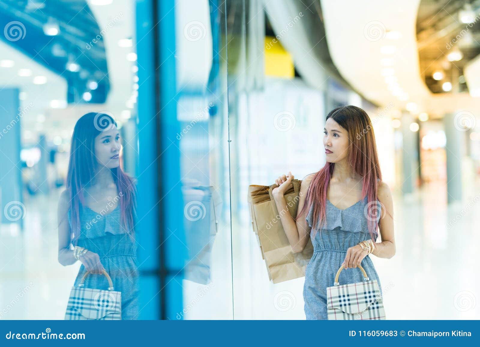 愉快的年轻加上走在mallConsumerism的购物袋
