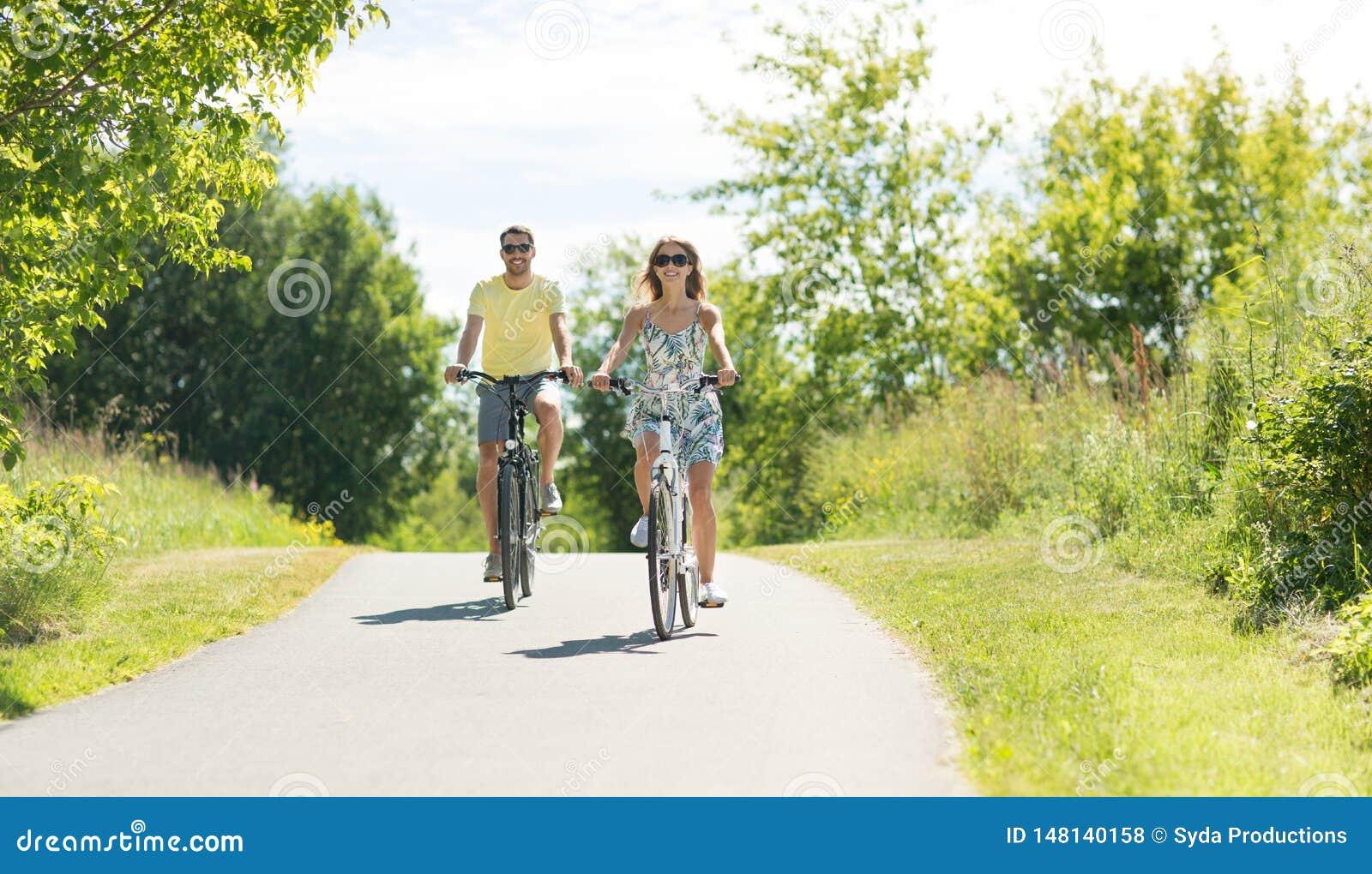 愉快的年轻夫妇乘坐的自行车在夏天