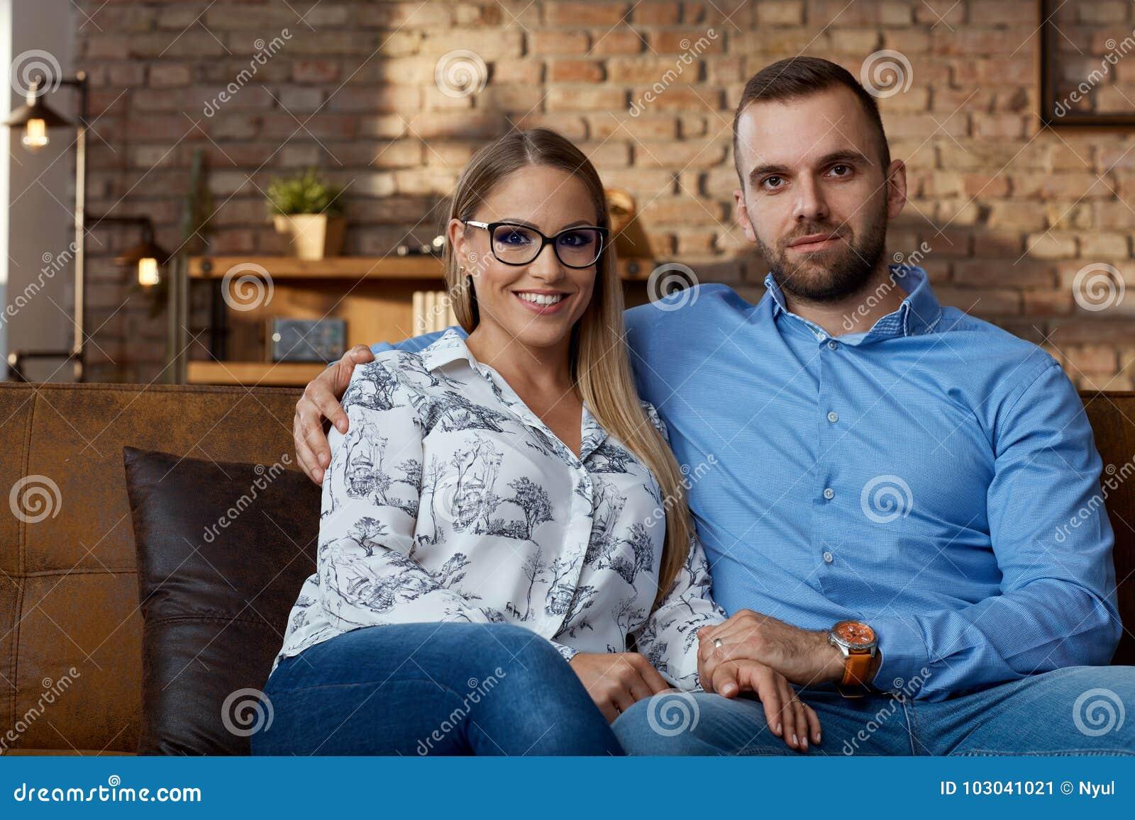 愉快的年轻夫妇在家坐长沙发