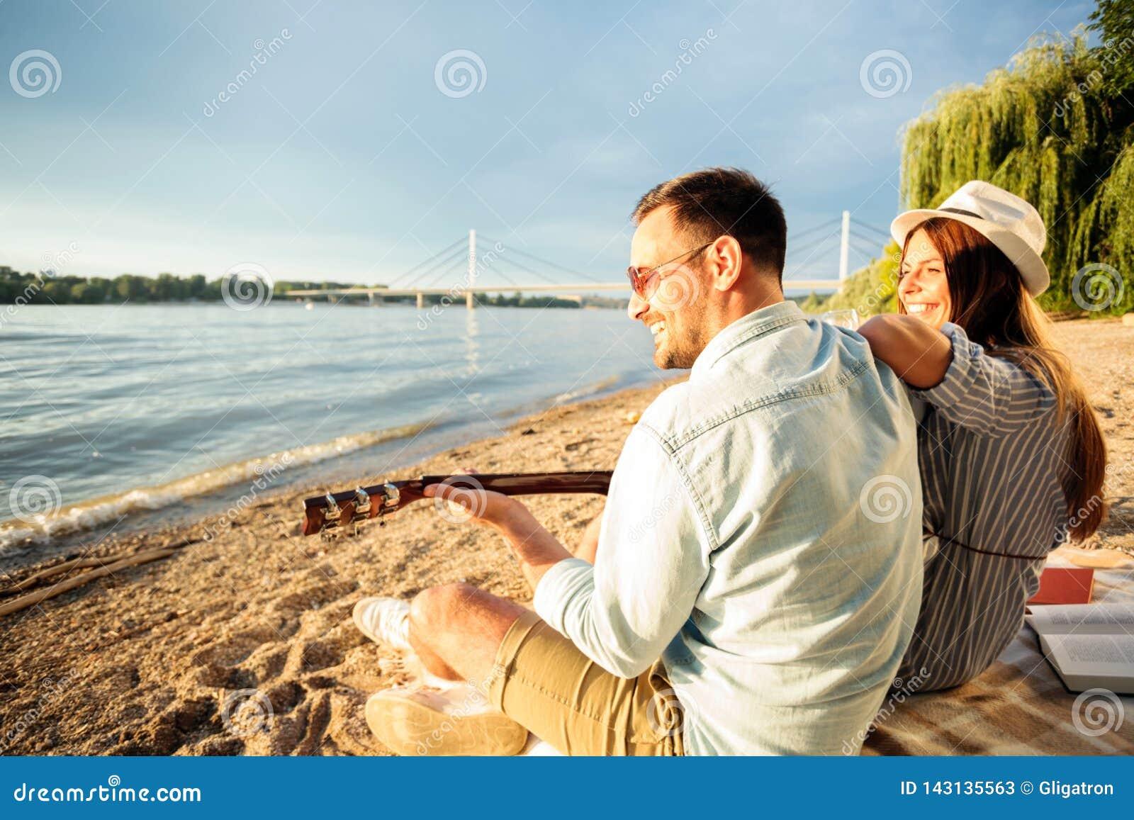 愉快的年轻夫妇有了不起的时光一起在海滩,弹吉他