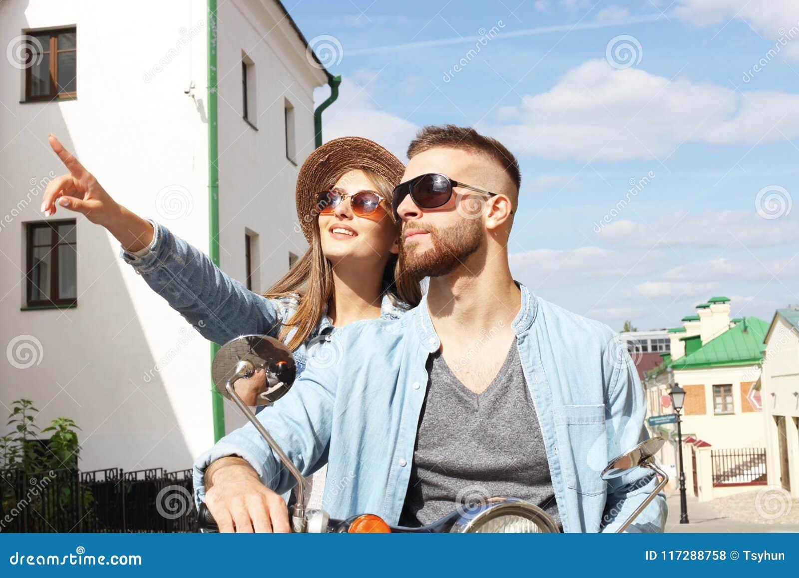 愉快的年轻夫妇骑马滑行车在镇里 英俊的人和少妇旅行 冒险和假期概念