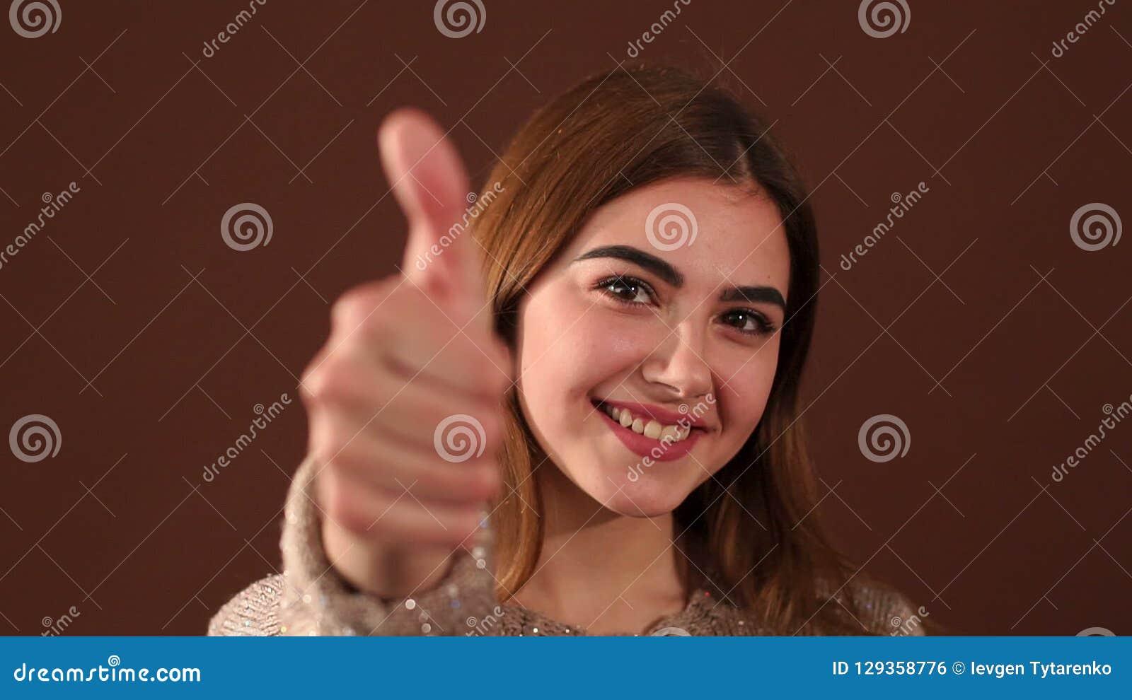 愉快的年轻成功的女孩显示在棕色背景的赞许 影视素材