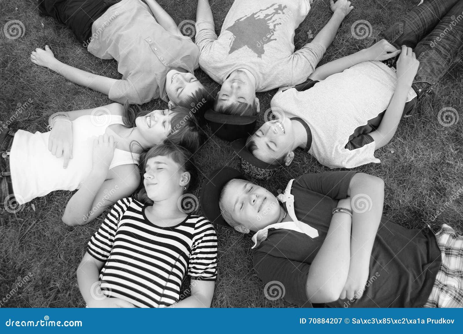 愉快的微笑的说谎在春天草的十几岁的男孩和女孩