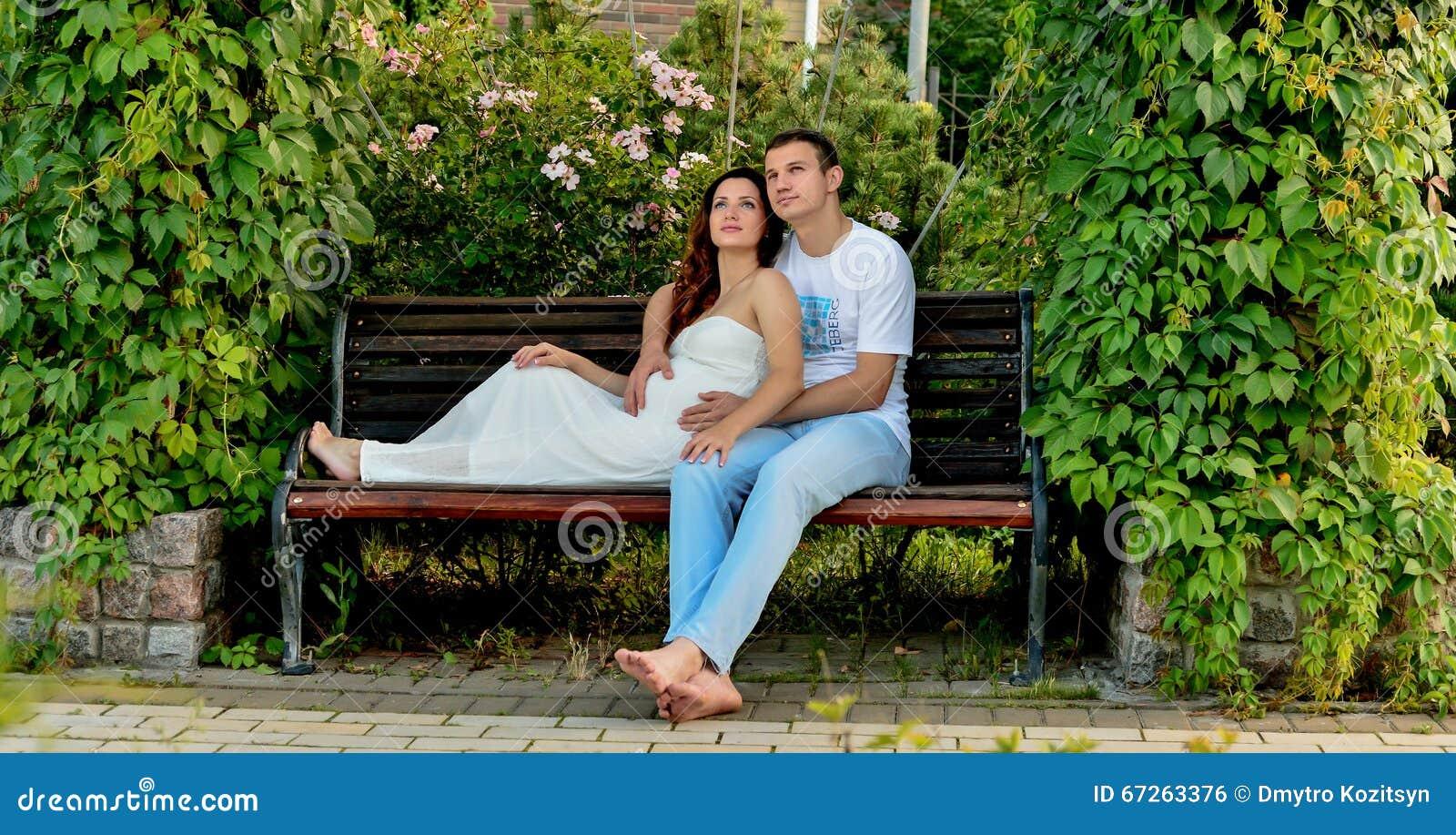 愉快的怀孕的夫妇坐banch在公园