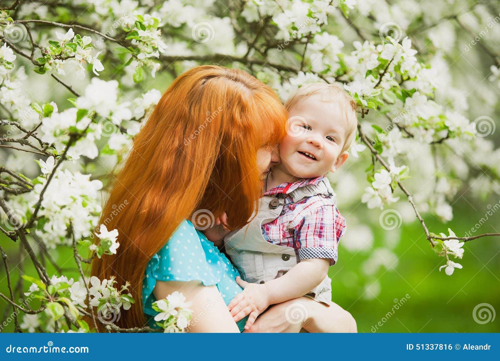 愉快的愉快的母亲画象和儿子在春天从事园艺