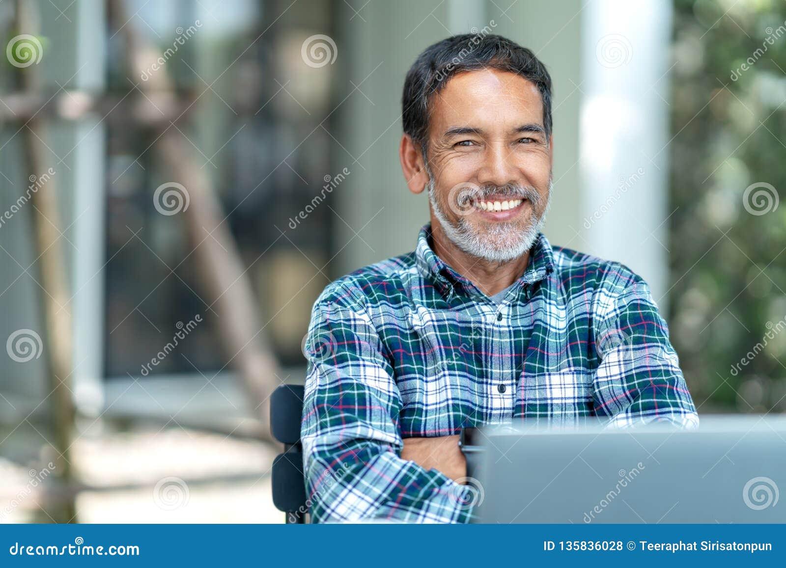 愉快的成熟人画象有看照相机的白色,灰色时髦的短的胡子的室外 退休的拉美裔偶然生活方式