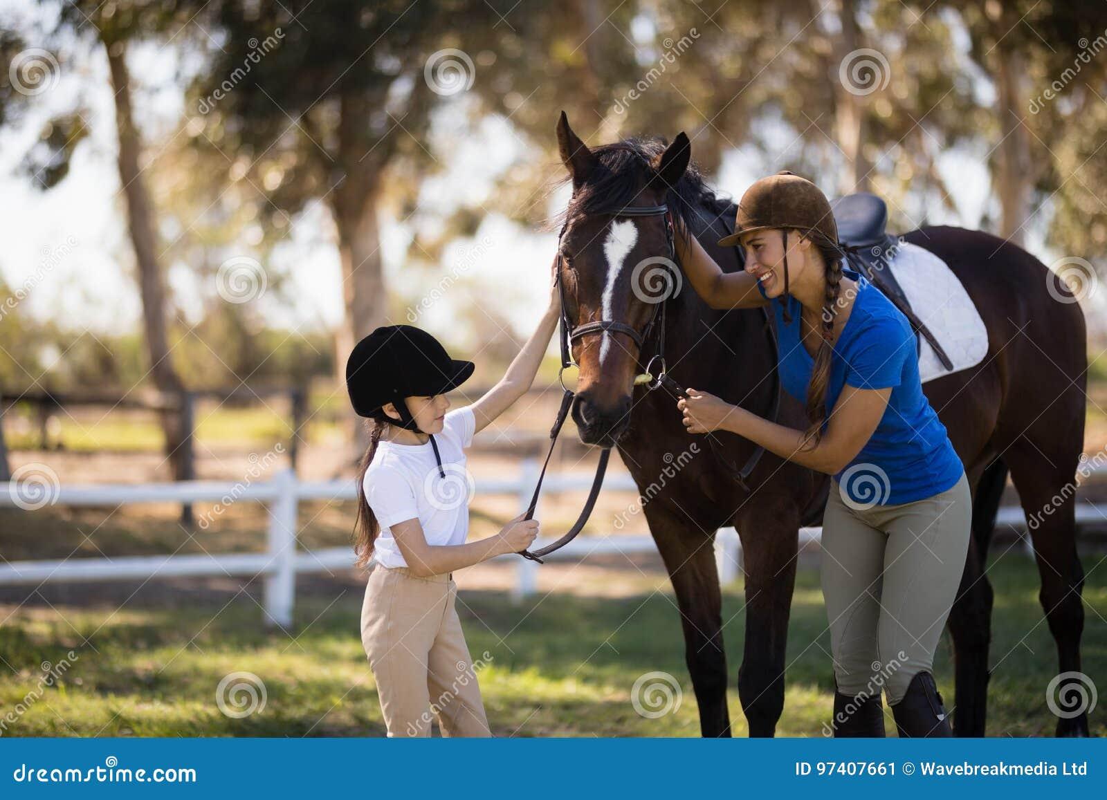 愉快的抚摸马的女孩和女性骑师
