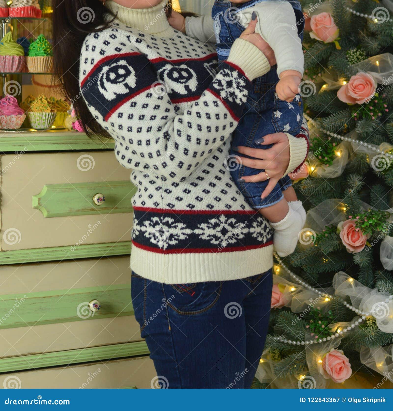 愉快的拿着中看不中用的物品的母亲和可爱的婴孩反对与圣诞树的国内欢乐背景