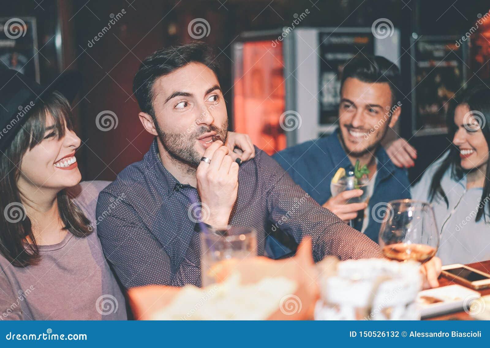 愉快的朋友有乐趣饮用的鸡尾酒在酒吧-一起笑和享受周末夜生活的年轻时髦人民