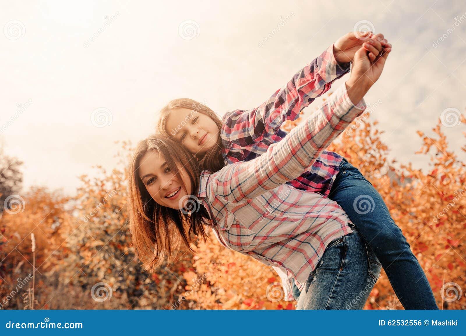 愉快的母亲和女儿舒适步行的在晴朗的领域