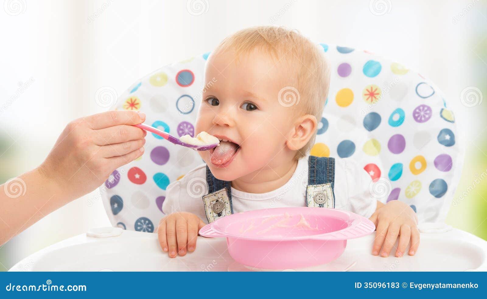愉快的母亲喂养从匙子的滑稽的婴孩
