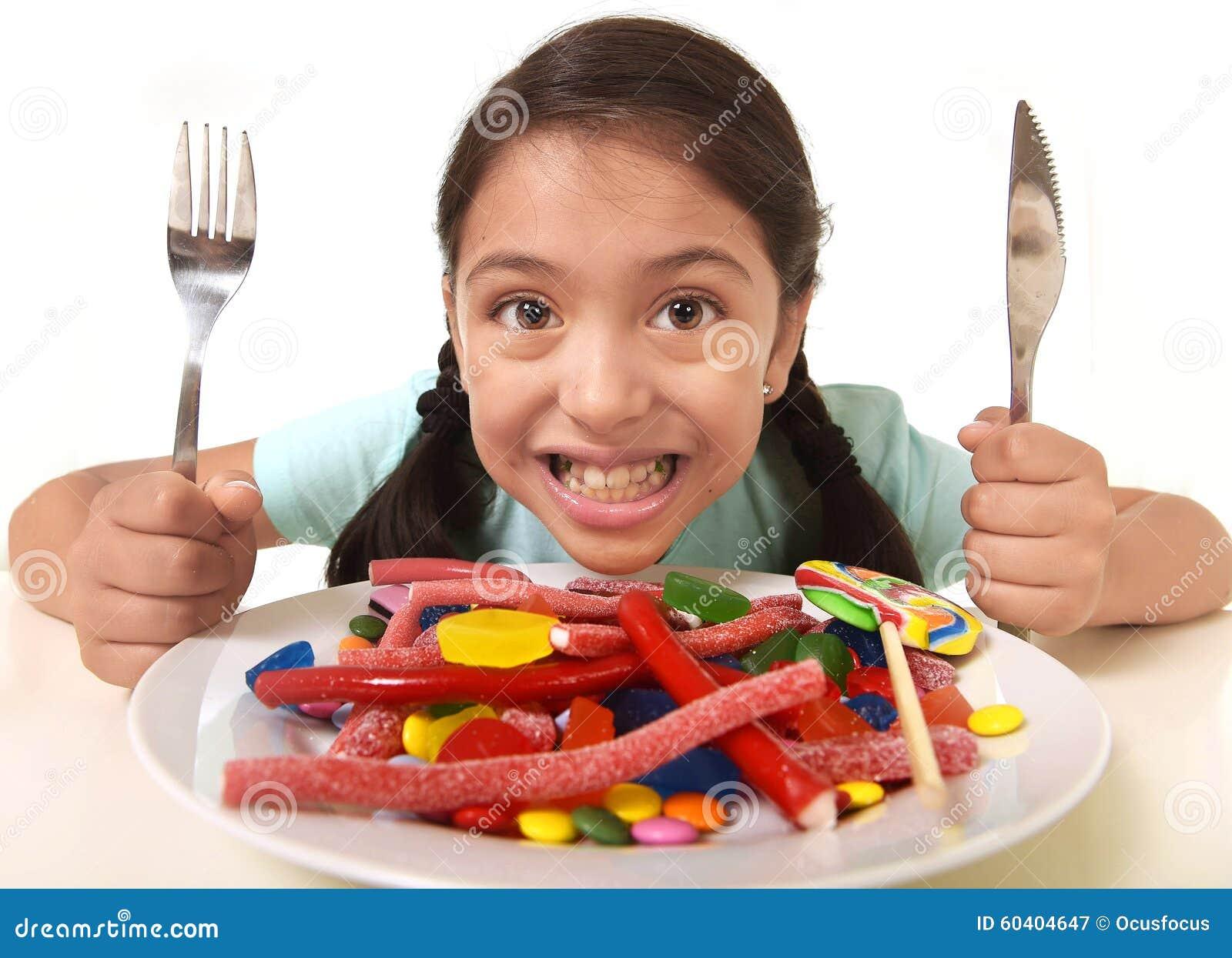 愉快的激动的拉丁坐在桌上的女孩拿着叉子的和刀子准备好为充分吃一个盘糖果