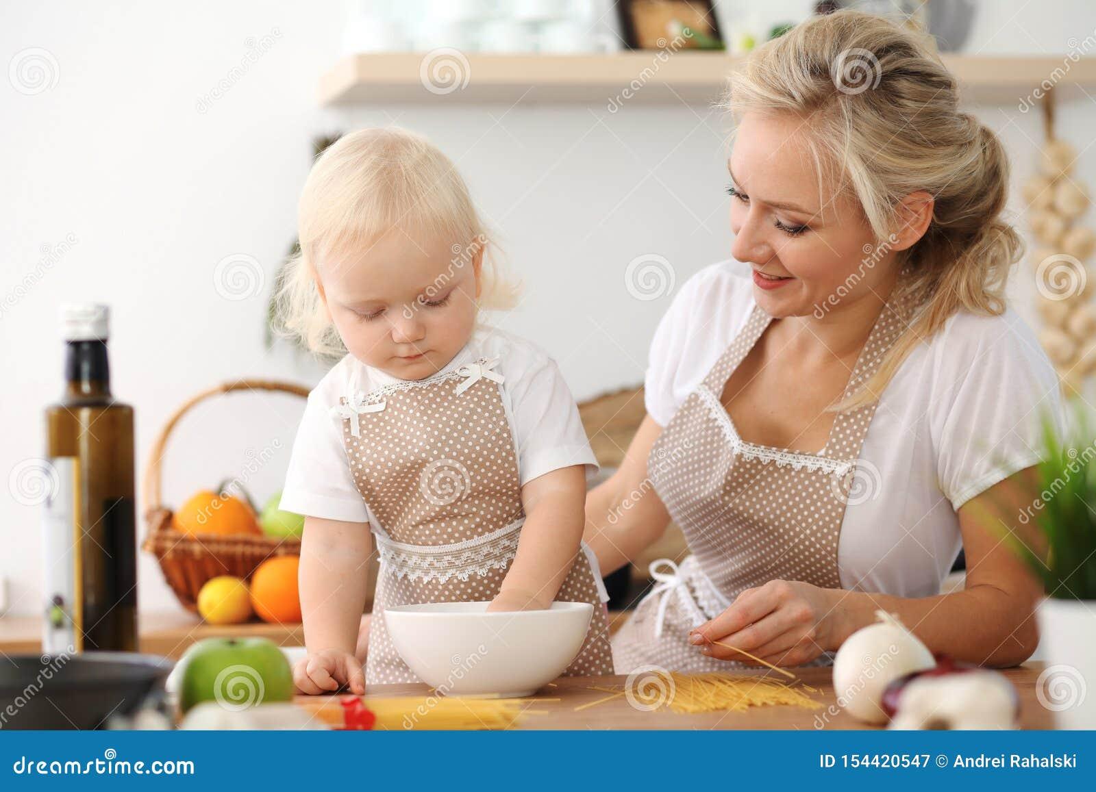 愉快的烹调在厨房里的母亲和小女儿 消费时间全部一起,家庭乐趣概念