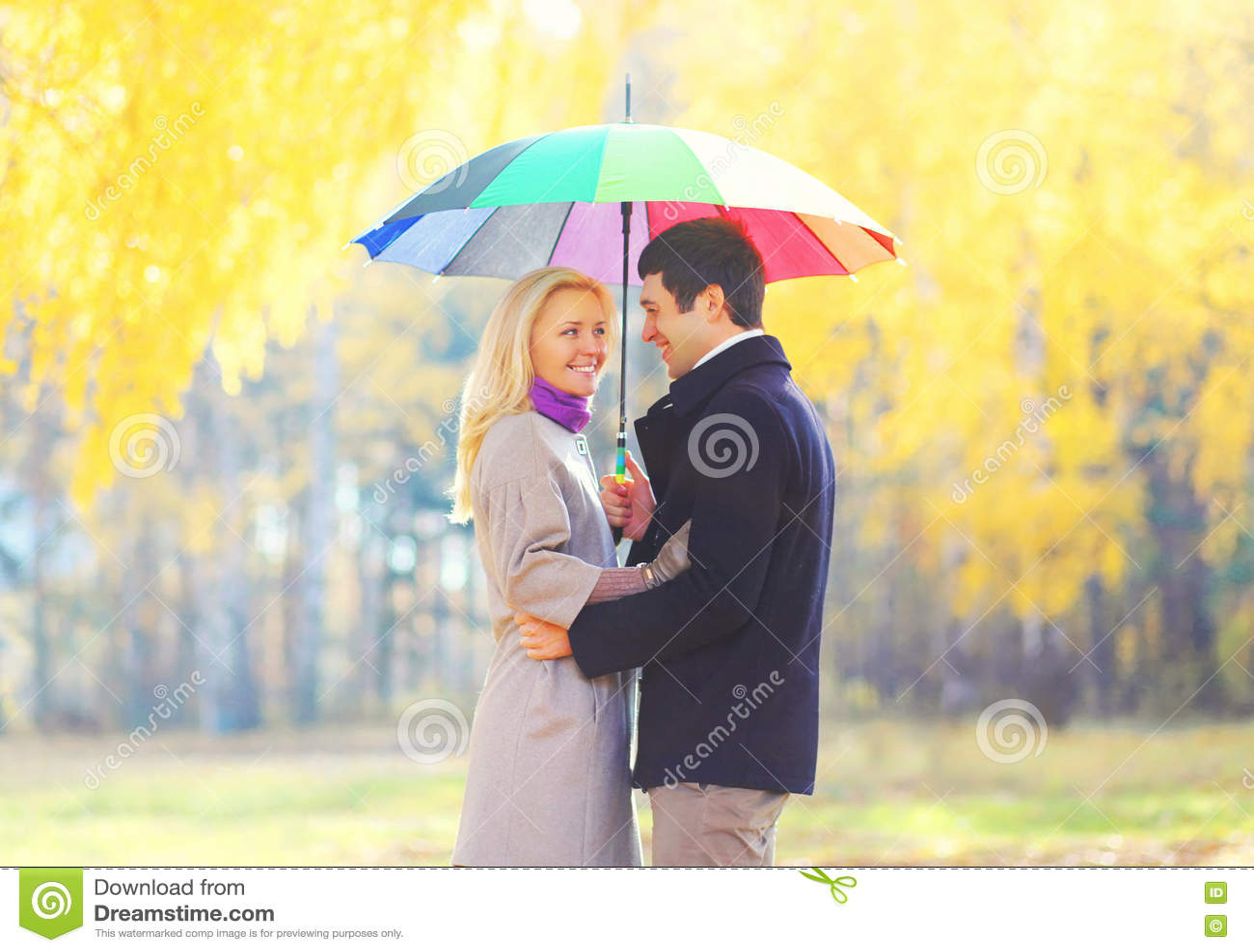 愉快的爱的微笑的加上在温暖晴朗的五颜六色的伞