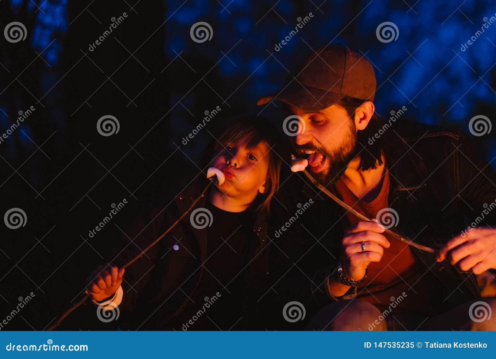 愉快的父亲和他的小儿子坐注册在火前面的森林和从的吃蛋白软糖
