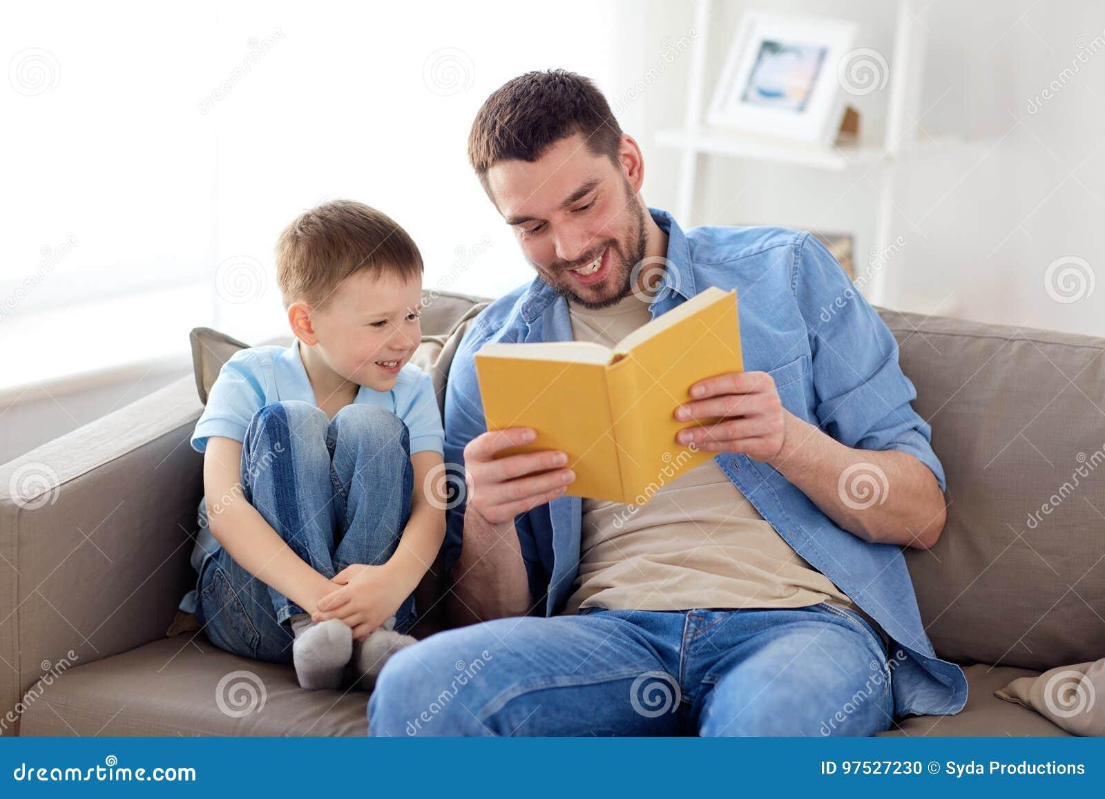 愉快的父亲和儿子阅读书沙发在家