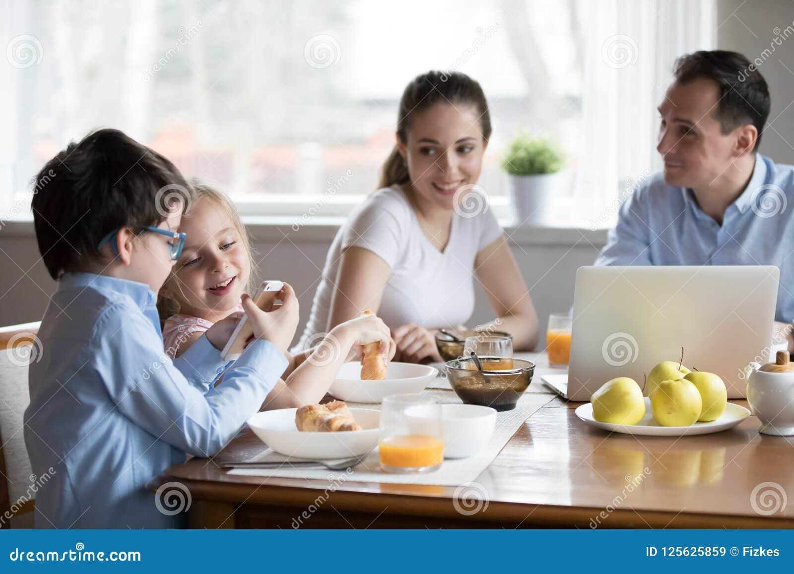 愉快的父母手表激发使用在kitche的智能手机的孩子