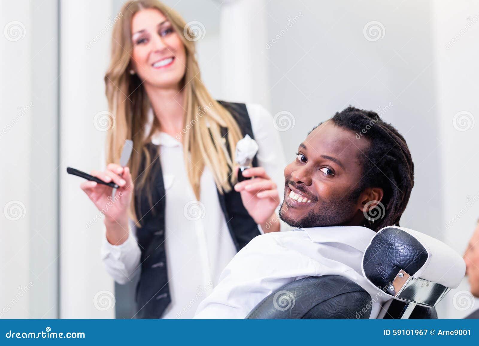 愉快的理发师和微笑的顾客沙龙的