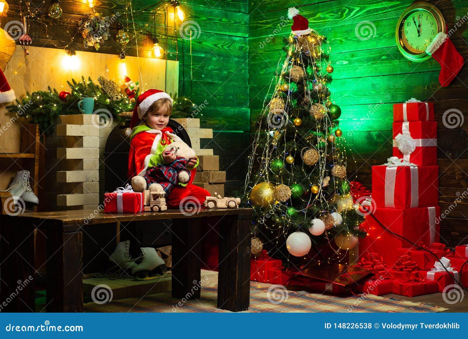 愉快的男孩使用与玩具由圣诞树 小孩穿圣诞老人衣裳 孩子等待新