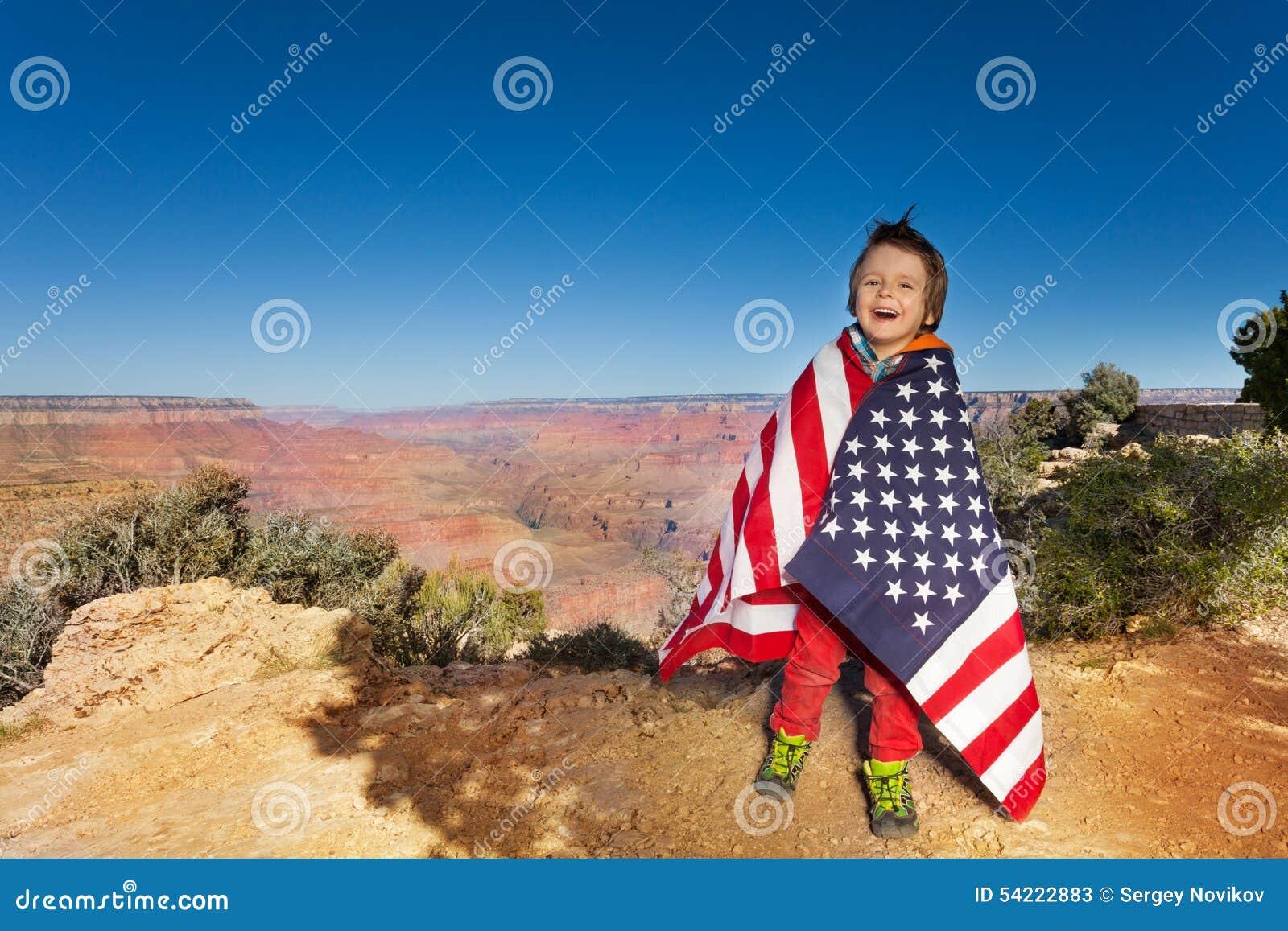 愉快的男孩在美国旗子,大峡谷包了