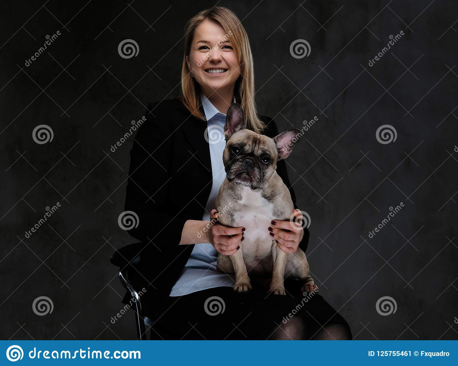 愉快的白肤金发的妇女交配动物者坐椅子和拿着她逗人喜爱的哈巴狗