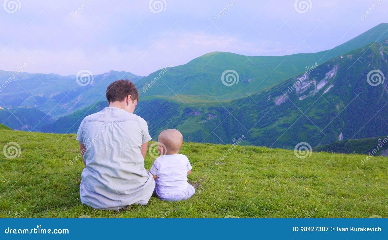 愉快的看起来向前和指向天空的母亲和她的孩子 家庭在山的迁徙的天