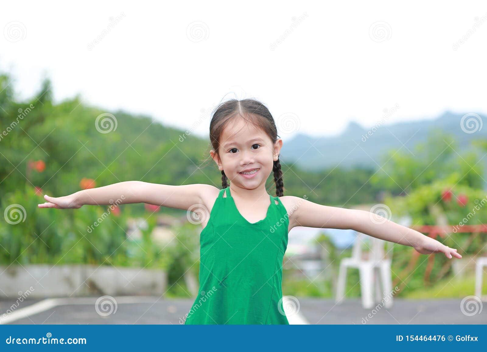 愉快的矮小的亚洲孩子女孩舒展在山坡武装并且放松