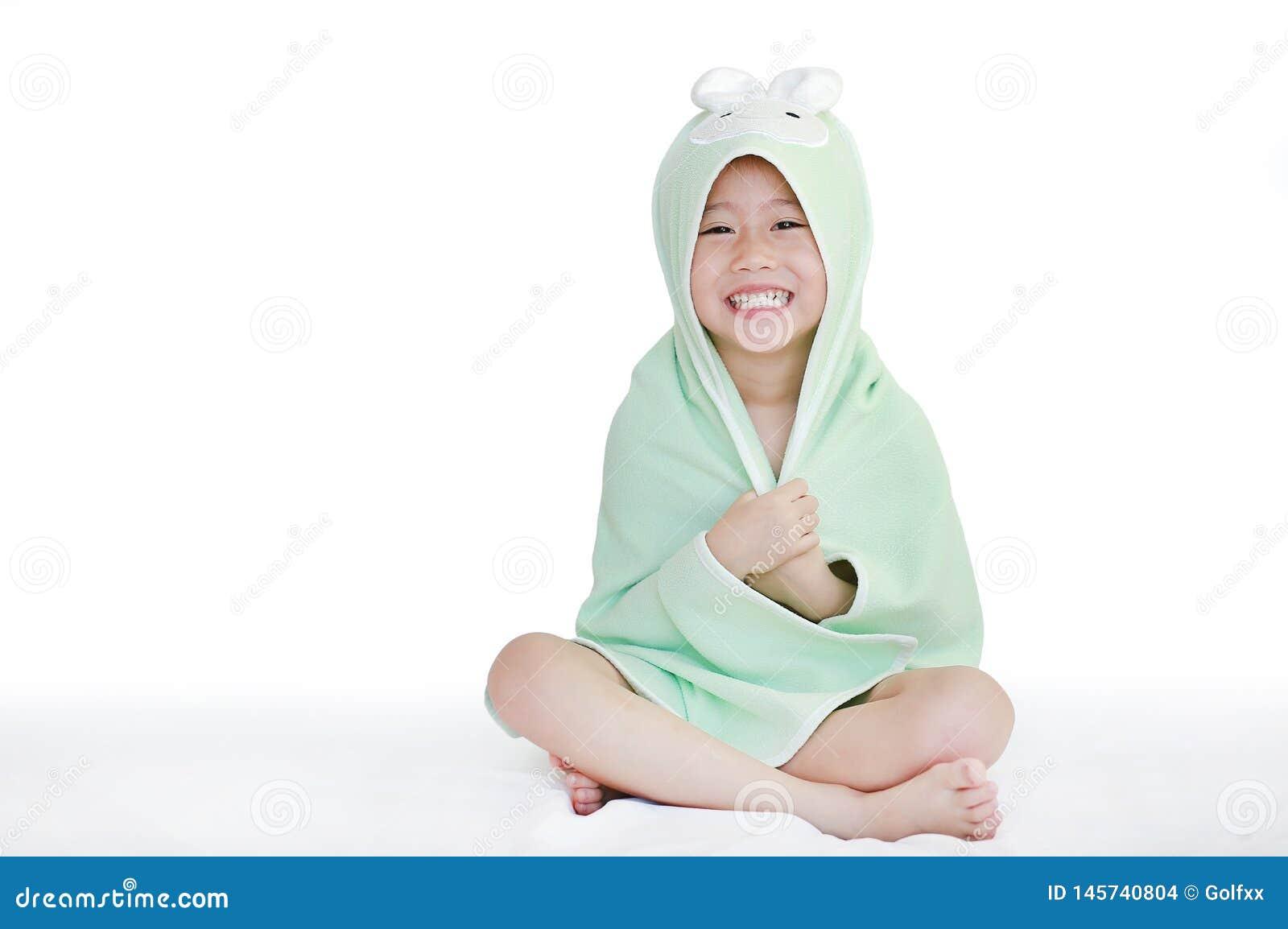 愉快的矮小的亚裔在毛巾下的儿童女孩微笑的盖子身体在浴以后坐床反对白色背景