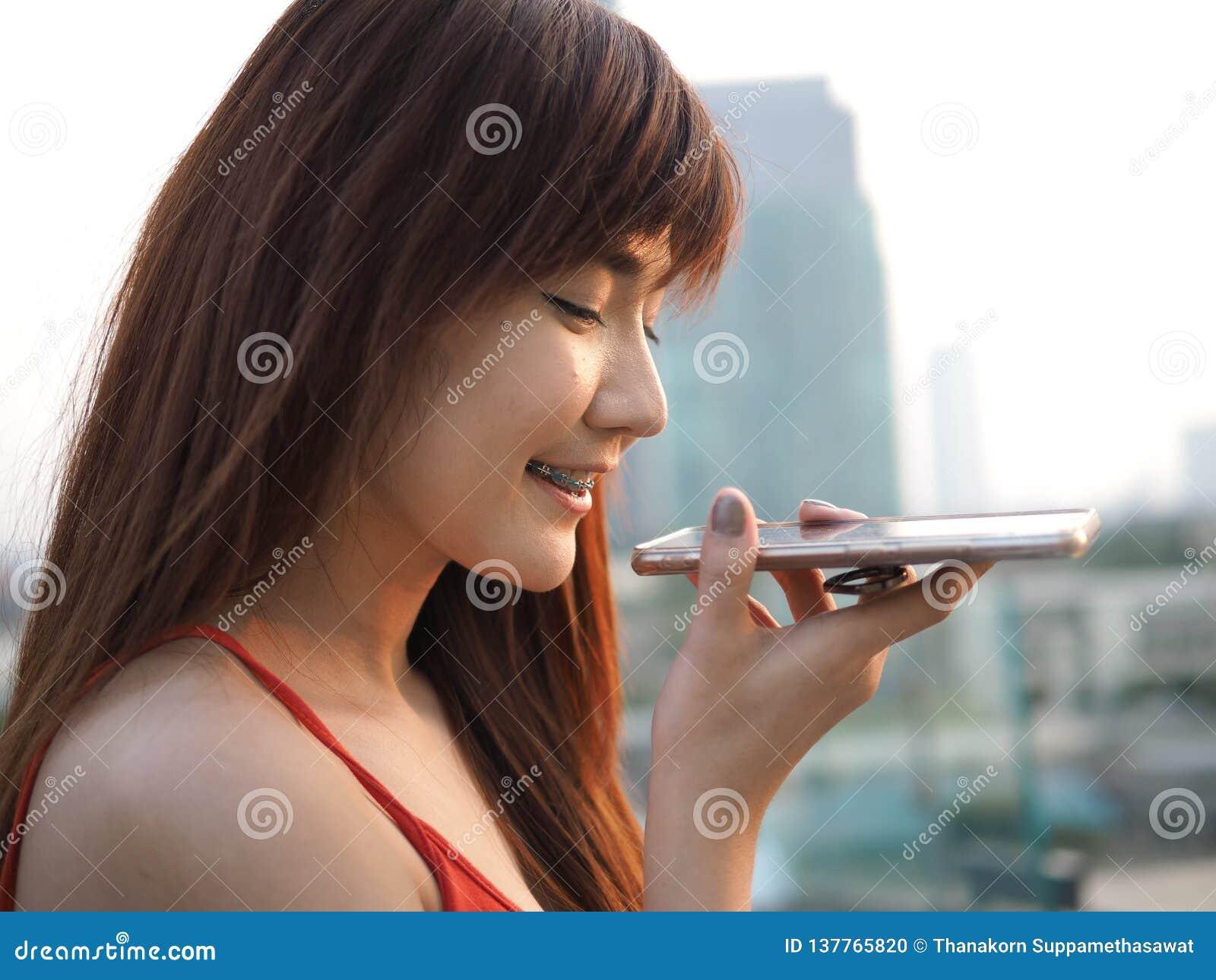 愉快的确信的妇女谈话在扬声麦克风的流动手机
