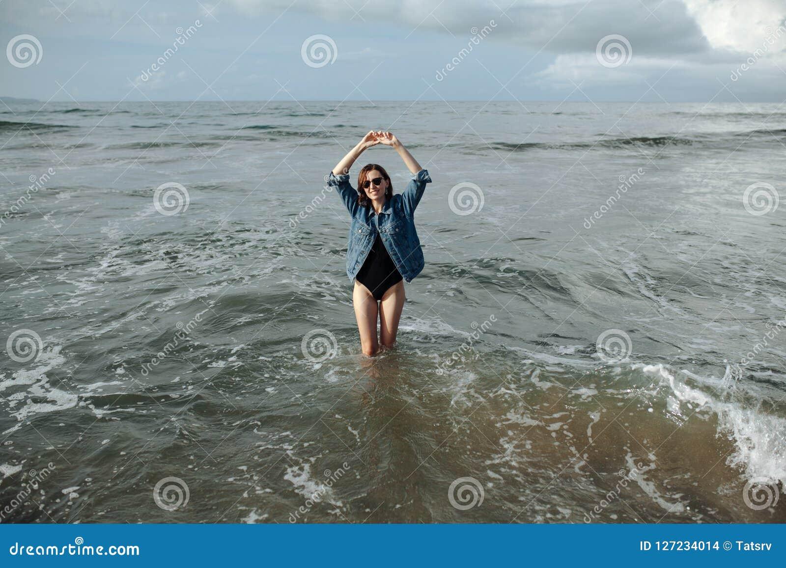 愉快的穿黑泳装和牛仔布夹克的微笑深色的妇女在海洋背景喜欢走在海洋,被举的手