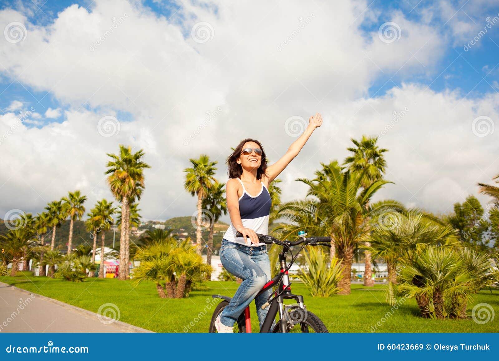 愉快的美丽的性感的女孩妇女骑马自行车用被举的手