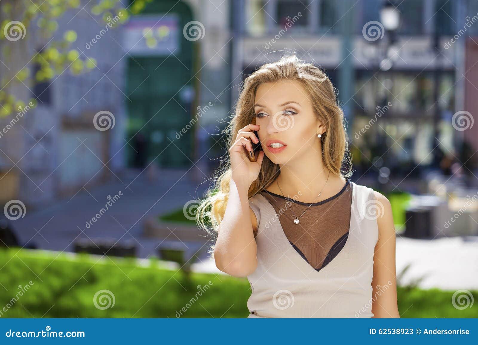 愉快的美丽的白肤金发的女孩叫由在夏天街道的电话