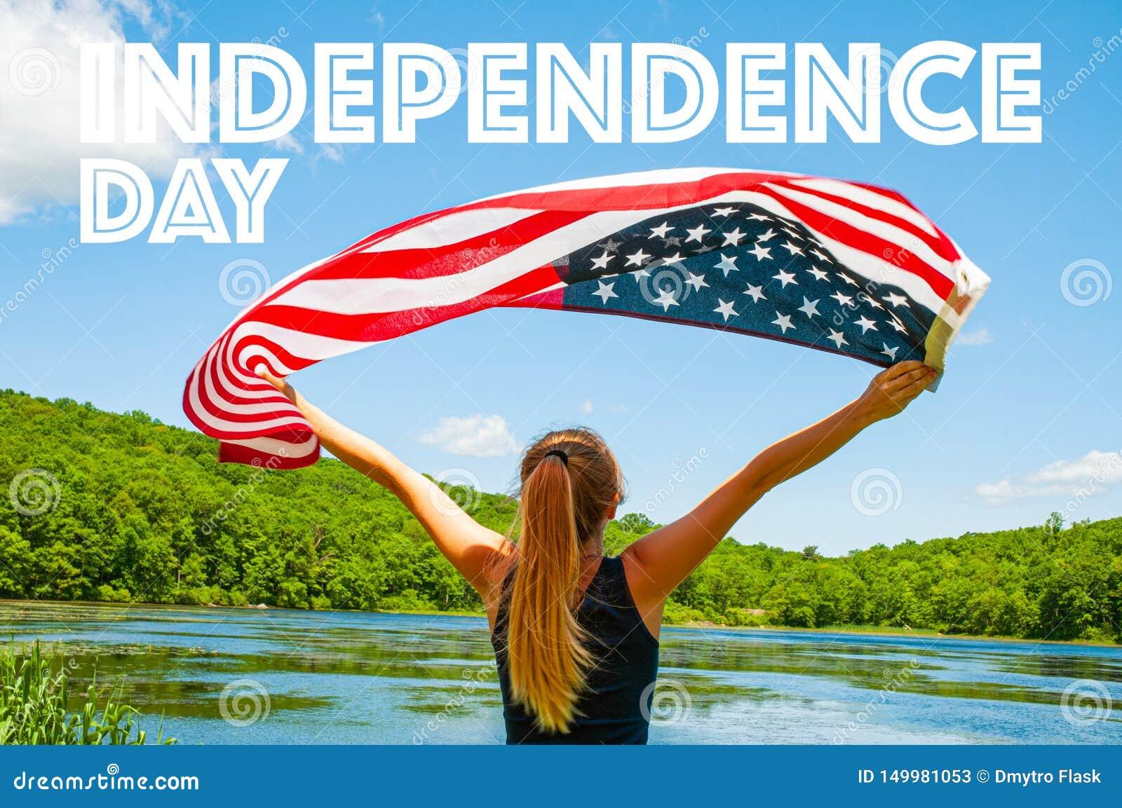 愉快的美国独立日,第4 7月 拿着在湖背景的妇女美国国旗