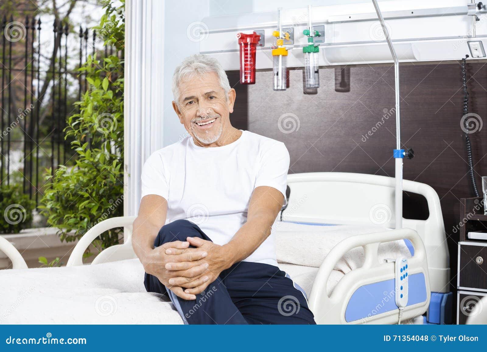 愉快的老人坐床在康复中心