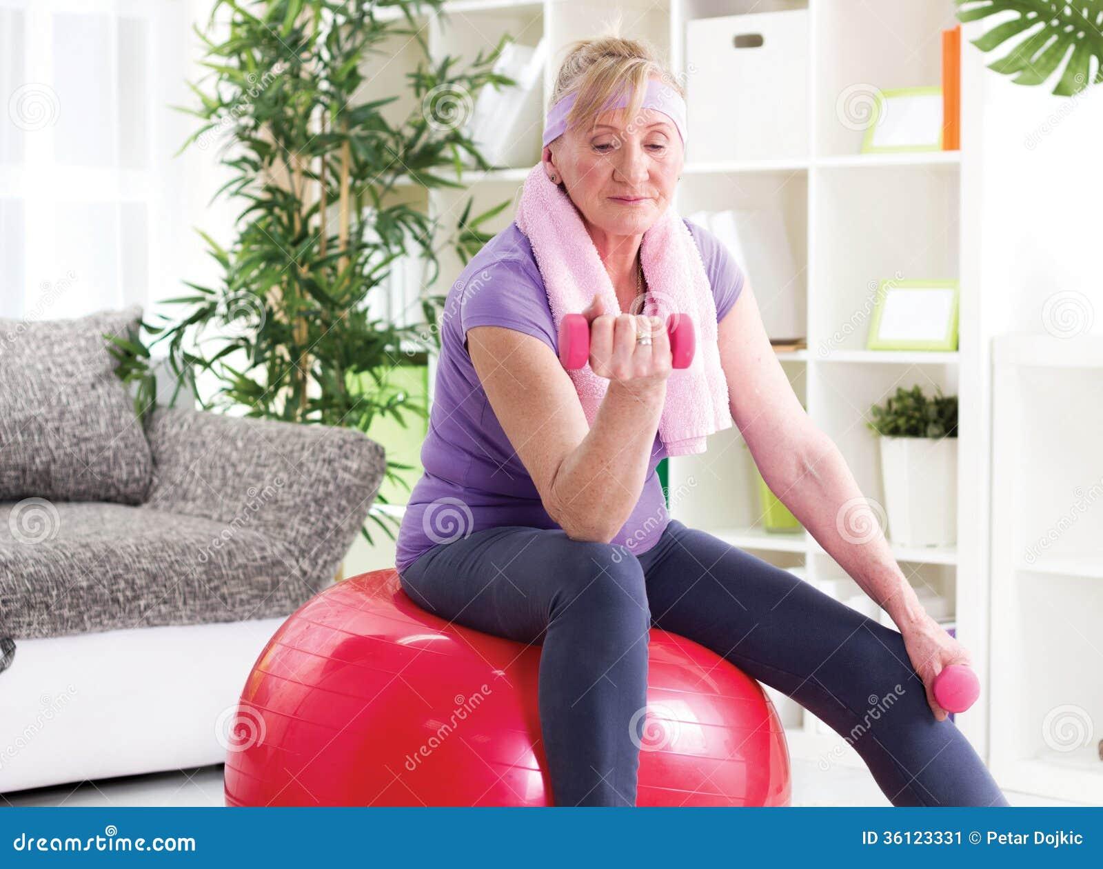愉快的资深与dumbbe的妇女坐健身房球和锻炼