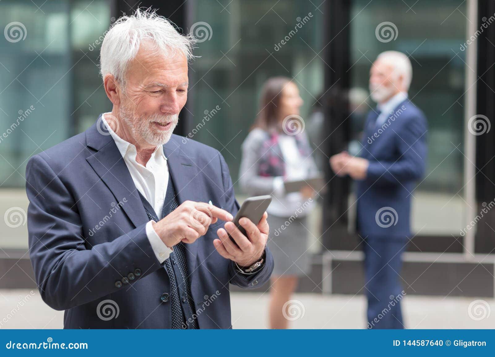愉快的资深商人浏览互联网或传讯在智能手机
