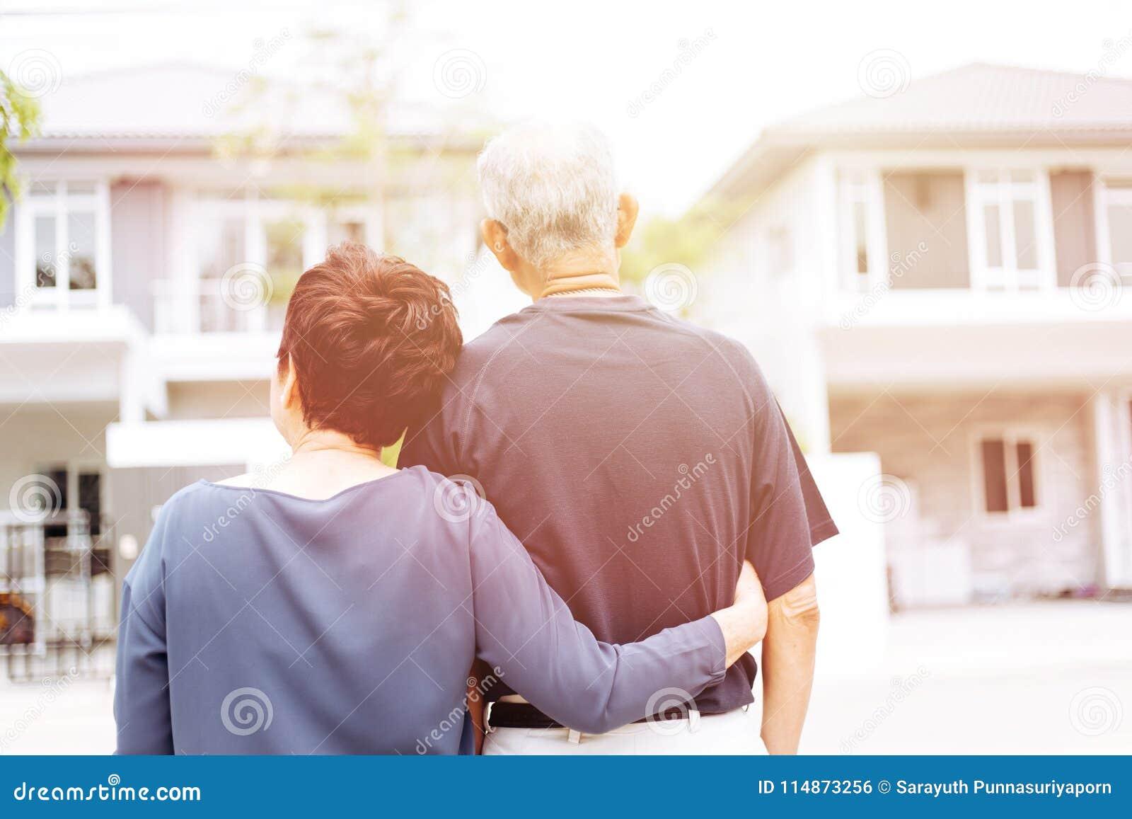愉快的资深夫妇从房子和汽车后面看的  与阳光的温暖的口气