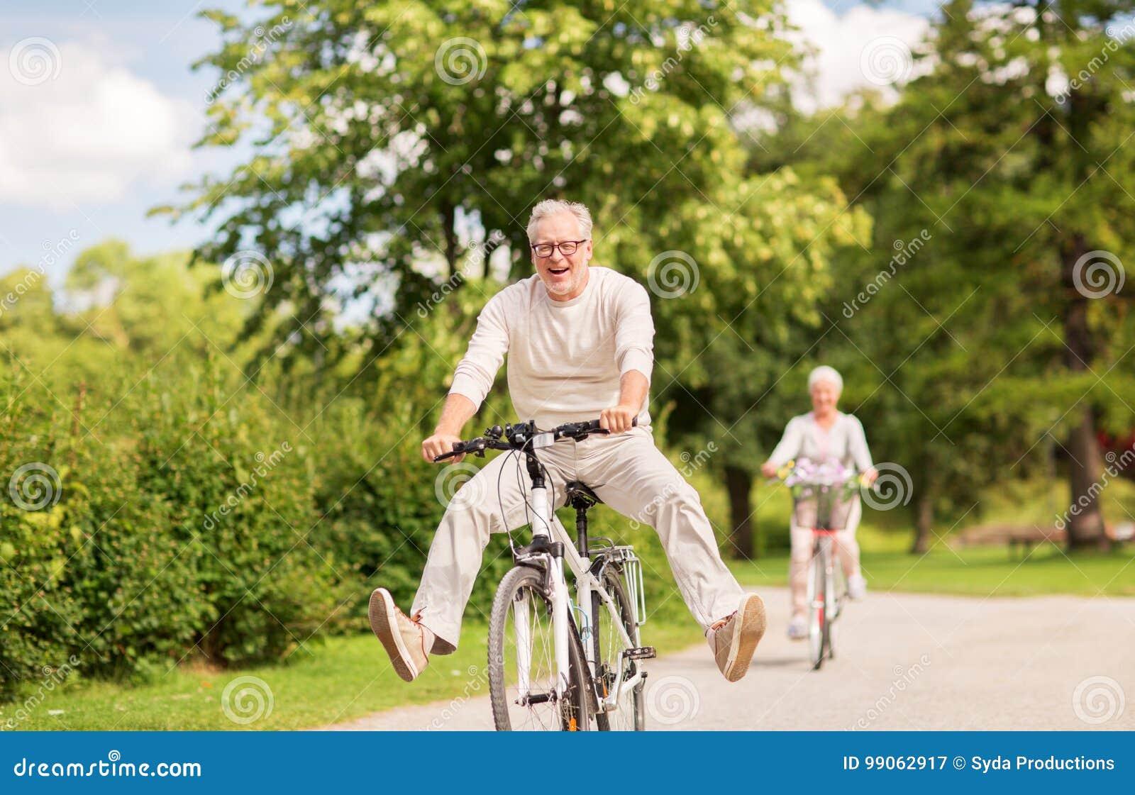 愉快的资深夫妇骑马在夏天公园骑自行车