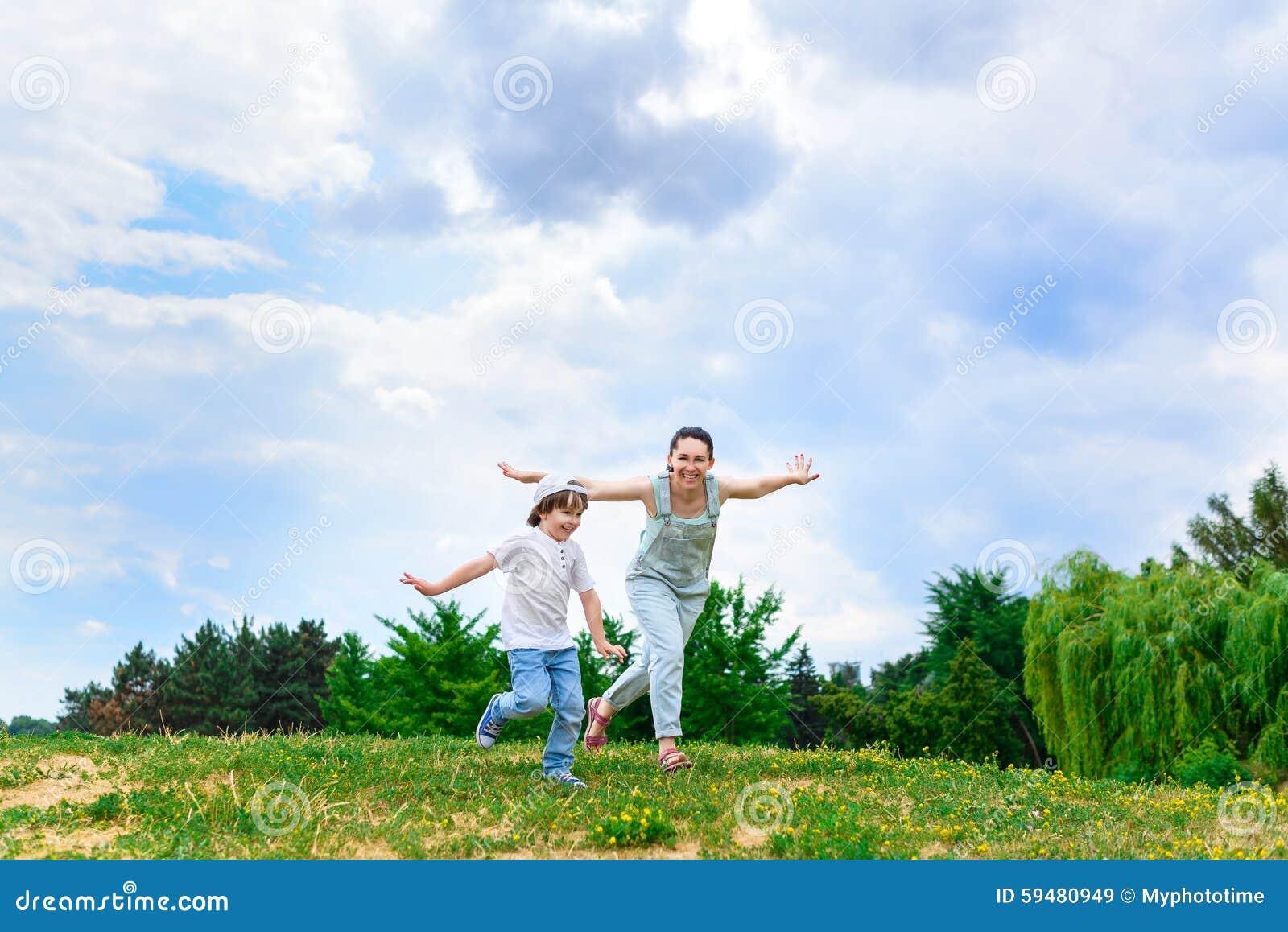 愉快的跑在草微笑的母亲和儿子