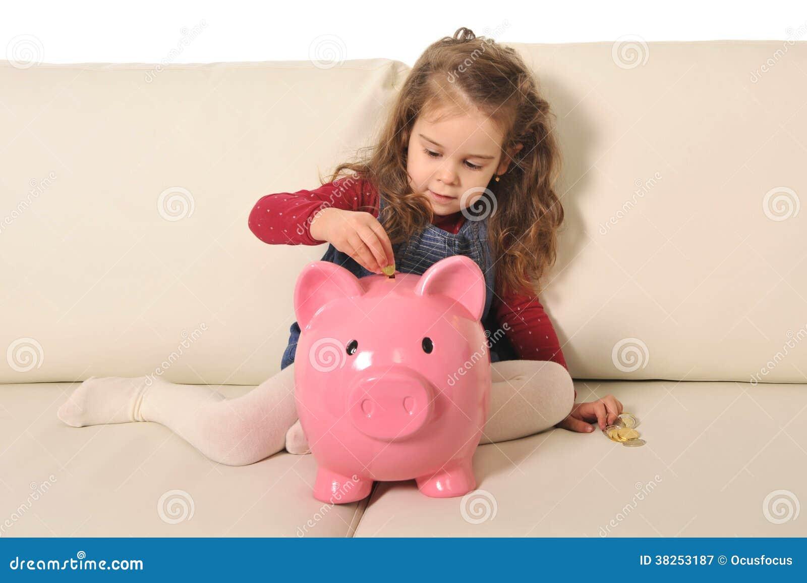 愉快的逗人喜爱的小女孩坐插入硬币的巨大的存钱罐