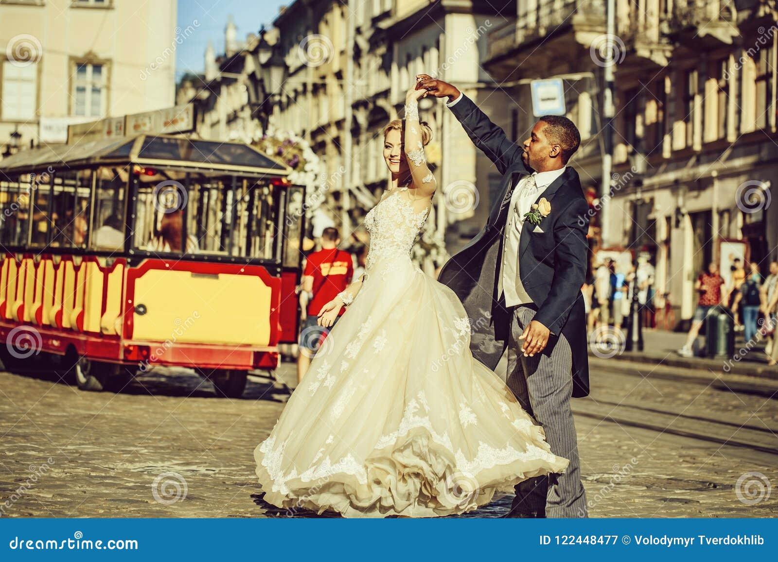 愉快的非裔美国人的新郎和逗人喜爱的新娘跳舞在街道上