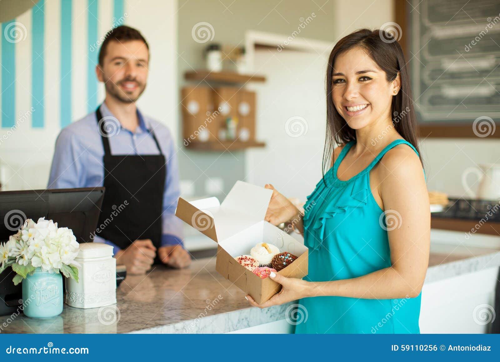 愉快的顾客在蛋糕商店