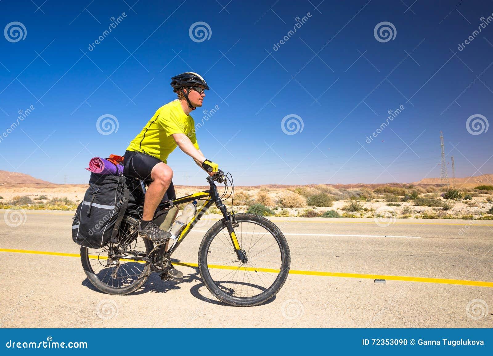 愉快的骑自行车的人在美丽的路放松在以色列沙漠 晴朗的热的天
