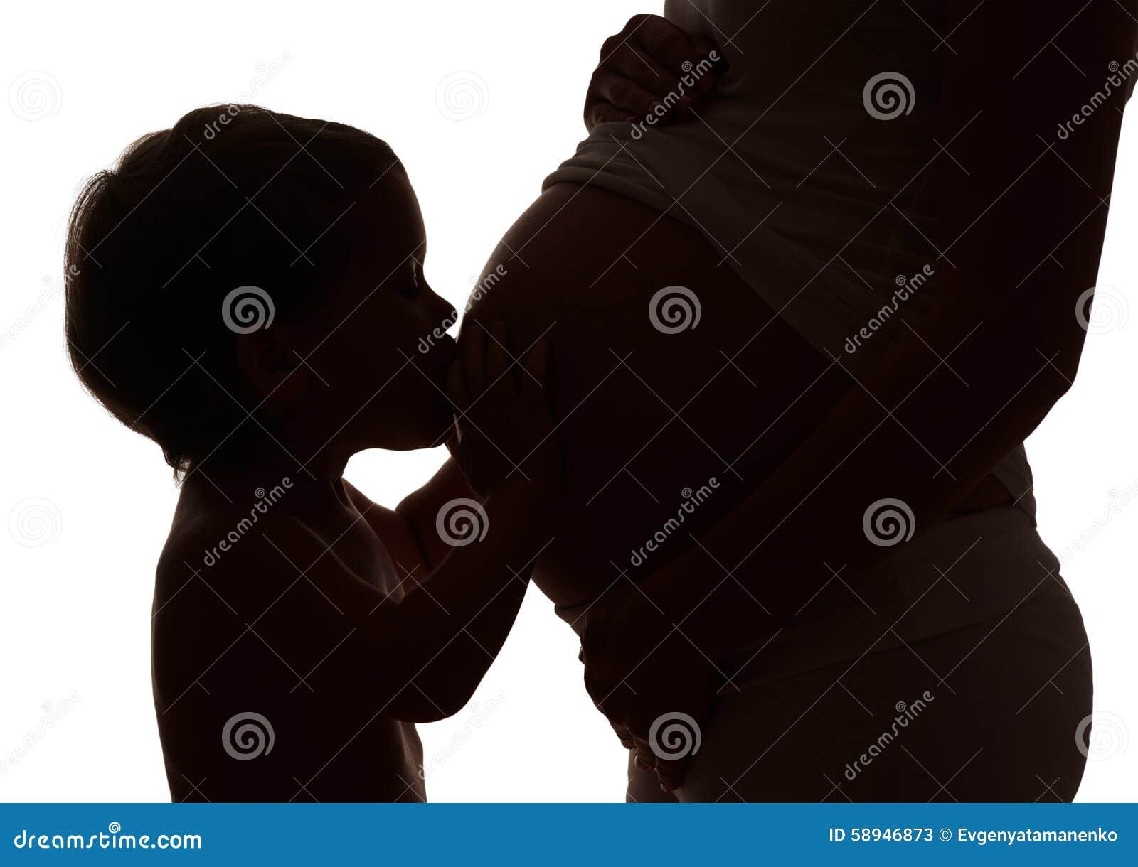 愉快的系列 愉快的怀孕的母亲的儿童亲吻的腹部剪影.图片
