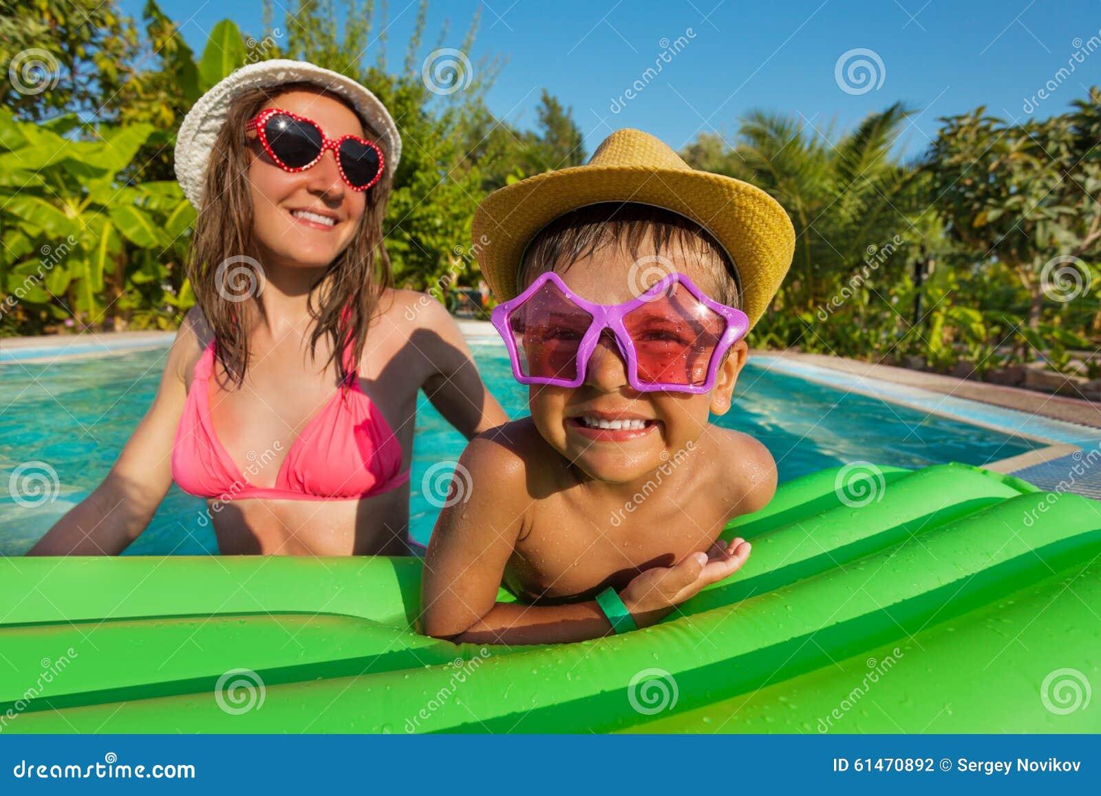 愉快的戴滑稽的太阳镜的母亲和男孩
