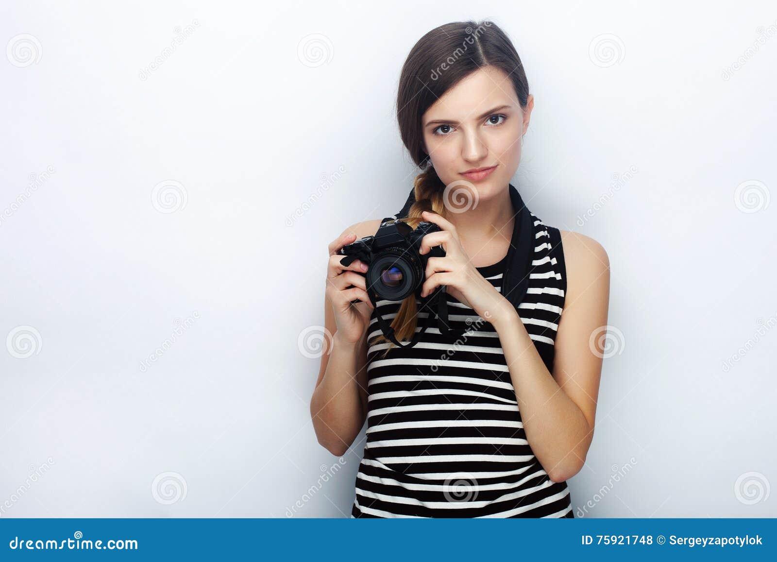 愉快的年轻美丽的妇女画象摆在与黑照片照相机的镶边衬衣的反对演播室背景