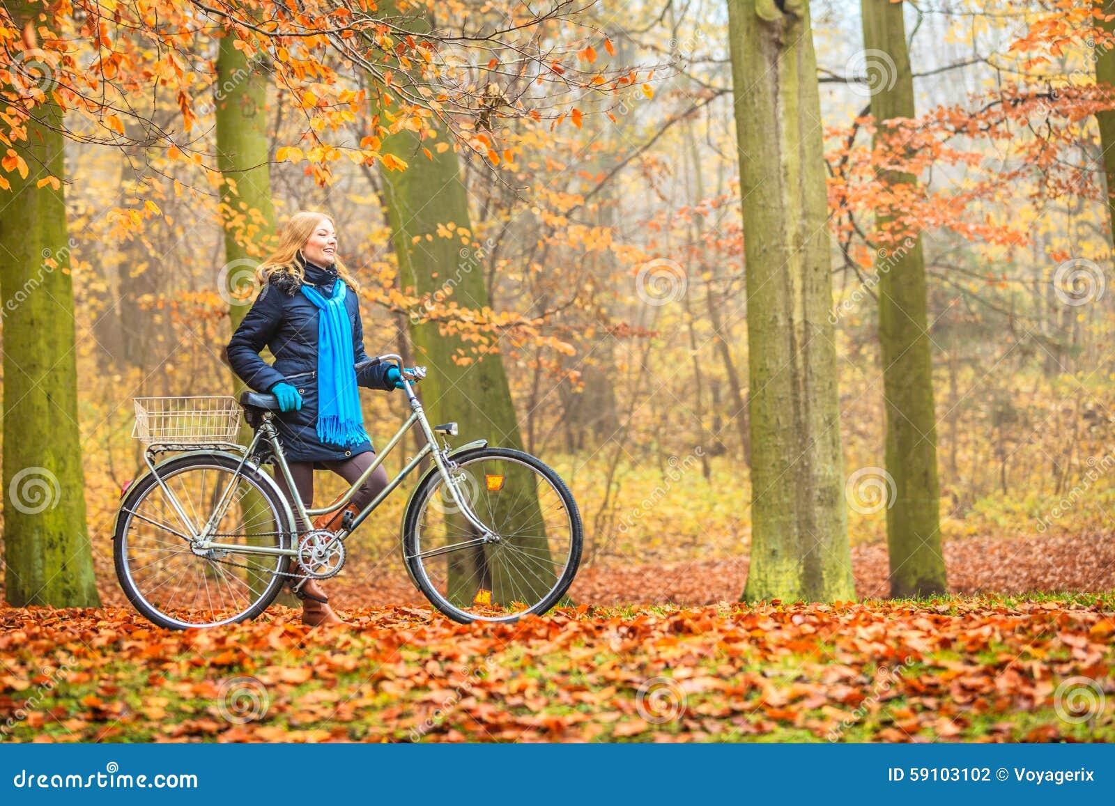 愉快的活跃妇女骑马自行车在秋天公园