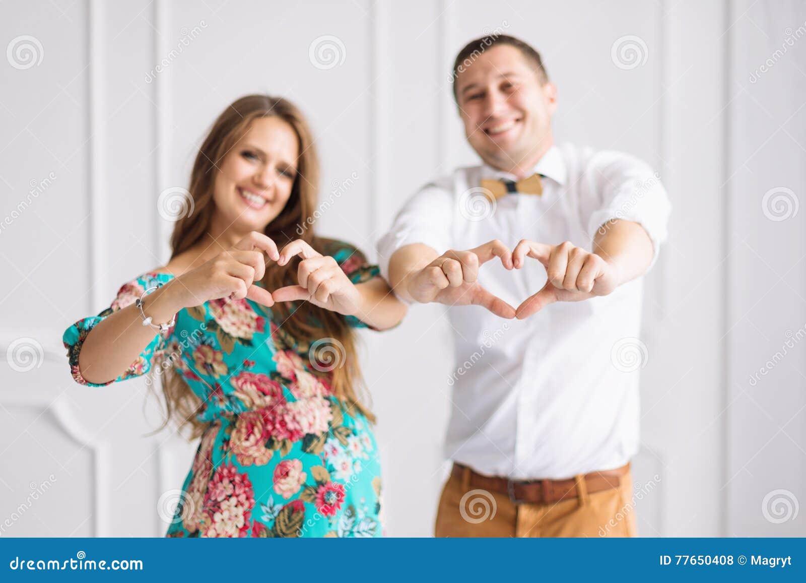 愉快美好的怀孕的夫妇一起期待孩子 男人和妇女在白色minimalistic内部显示的心脏用手
